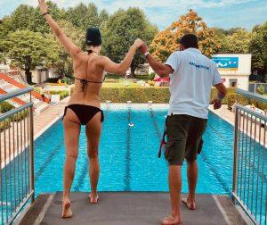 Mann und Frau sind dabei vom Sprungturm ins Wasser zu hüpfen
